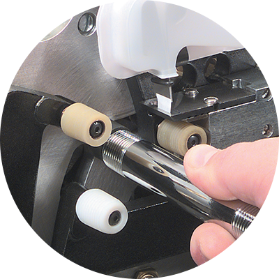 Hand inserting an unwrapped fitting into the Thred Taper machine.